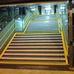 yellow handrails on station stairs